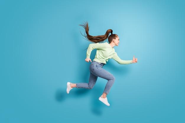 Фото сбоку в полный рост, прыгающая быстро бегающая девушка с длинными волосами, хвостиком, изолированными на ярко-синем цветном фоне