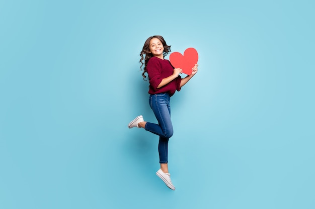 Full length body size side profile photo of schoolgril jumping up holding big red heart smiling toothily in burgundy sweater receiving present gift isolated blue vivid color background