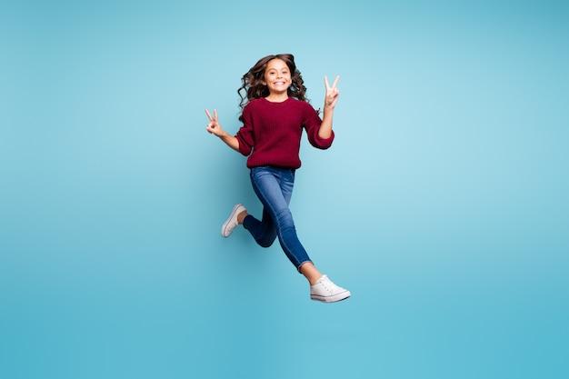 전체 길이 몸 크기는 v-sign 이중 절연 생생한 컬러 배경을 보여주는 데님 신발 부르고뉴 스웨터를 입고 쾌활한 재미 펑키 긍정적 인 소녀의 사진을 돌렸다