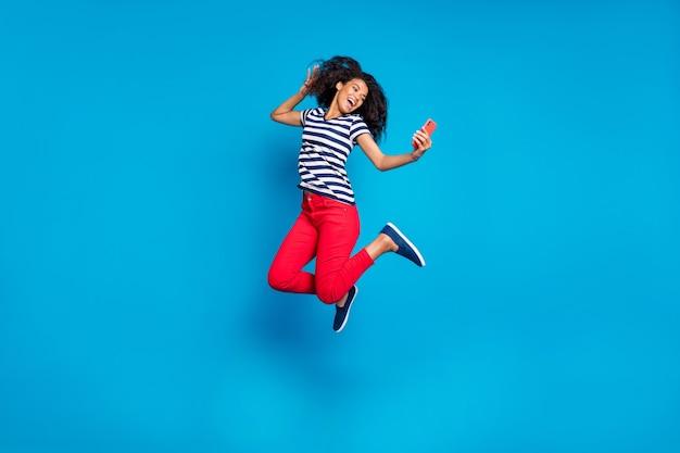 Полная длина тела повернутая фотография веселой позитивной симпатичной кудрявой волнистой красивой подруги, прыгающей в полосатой футболке, красных штанах, делающей селфи, изолированный яркий синий цвет