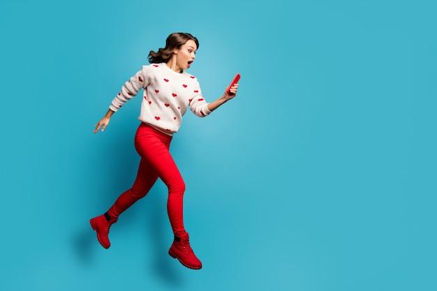 全身サイズのビューガジェットを使用してジャンプする驚いた感動した女の子急いで走っている偽のニュースを読んで