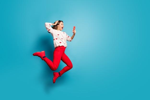 フルレングスのボディサイズビュー5gアプリの高速接続を使用して楽しんでジャンプする陽気な嬉しい女の子