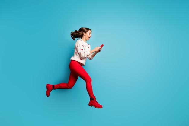 フルレングスのボディサイズビュー陽気な嬉しい女の子が高速急いで急いで実行している5gアプリを使用して楽しんでジャンプ