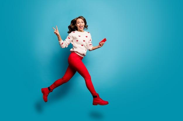 フルレングスのボディサイズビュー陽気な嬉しい女の子がガジェットを使用してジャンプ急いで急いでvサインを楽しんで表示