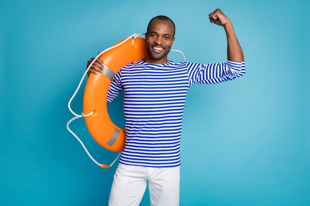 Full length body size view of cheerful guy carry rubber lifesaver isolated over blue background