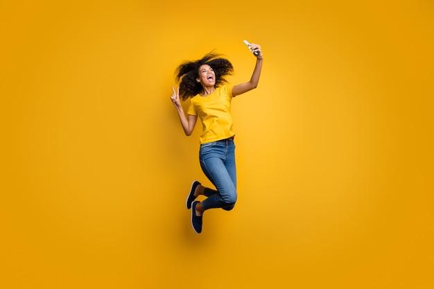 Вид в полный рост, девушка прыгает, принимая селфи на телефоне, сотовом смартфоне, показывая v-знак