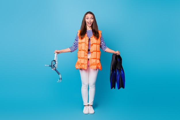 Full length body size view of her she attractive amazed cheerful cheery girl wearing float vest holding in hands scuba accessory mask flippers isolated bright vivid shine vibrant blue color background