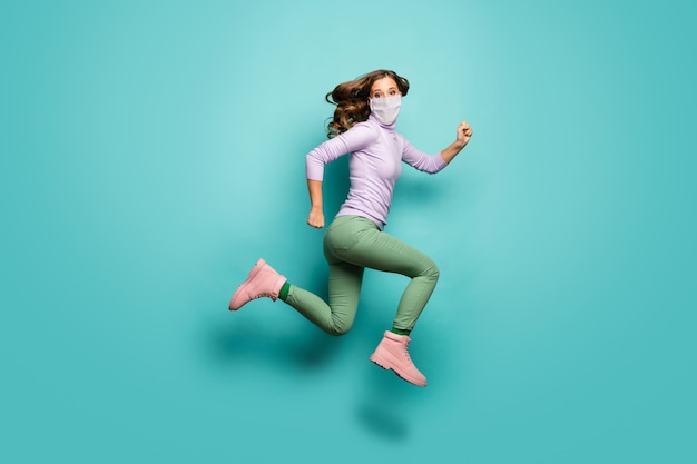 Full length body size view of her she attractive girl wearing safety mask jump run healthcare pandemia mers cov influenza disease prevention active life isolated teal pastel color background