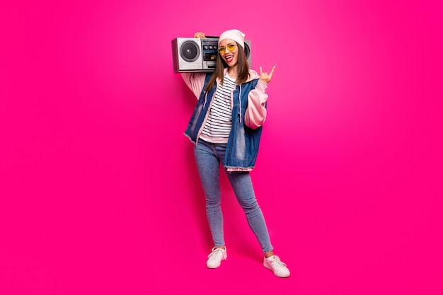 Full length body size view of her she nice attractive funky cool cheerful cheery girl carrying boombox showing horn sign having fun isolated on bright vivid shine vibrant pink fuchsia color