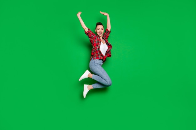 Full length body size view of her she nice attractive glad cheerful cheery girl in checked shirt jumping rising hands up having fun isolated on bright vivid shine vibrant green color background