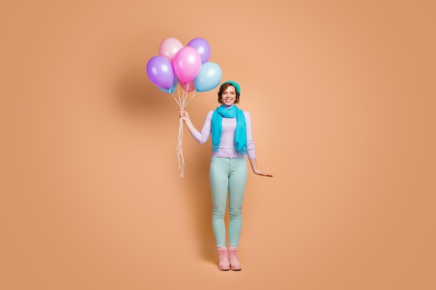 Full length body size view of her she nice attractive lovely pretty charming glad cheerful cheery girl holding in hands bunch air balls isolated over beige pastel color background