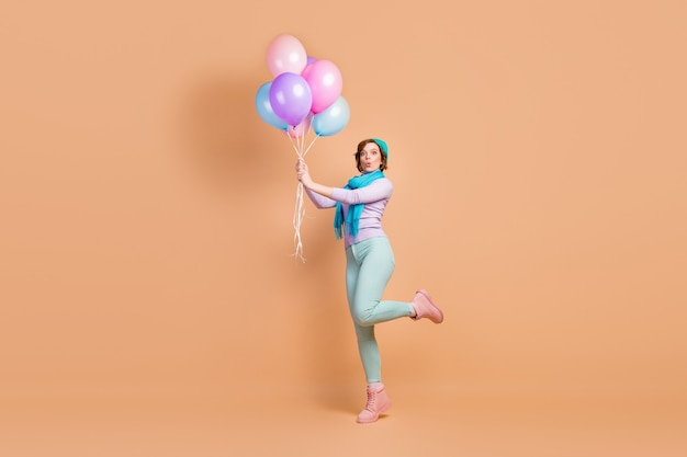 Full length body size view of her she nice attractive lovely pretty girlish funny dreamy cheerful cheery girl having fun holding in hands air balls isolated over beige pastel color background