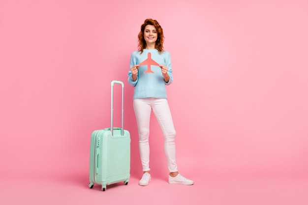 Full length body size view of her she nice attractive pretty cheerful wavy-haired girl holding in hands paper plane form departing holiday isolated over pink pastel color background
