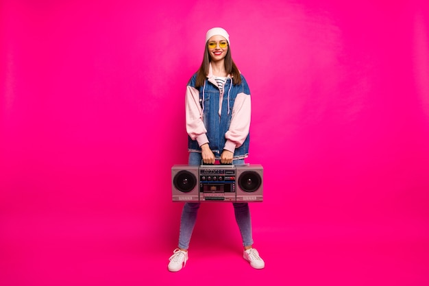 Full length body size view of her she nice attractive pretty cool cheerful cheery girl carrying boom-box having fun holiday isolated on bright vivid shine vibrant pink fuchsia color