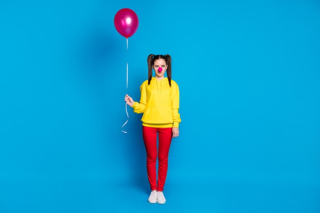 Full length body size view of her she nice attractive sad bored girl circus carnival clown holding in hand helium ball isolated over bright vivid shine vibrant blue color background