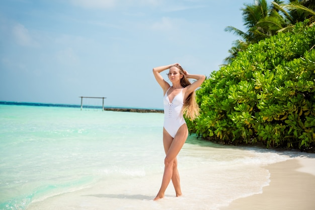 Full length body size view of her she nice attractive sporty thin slim fit slender girl model walking enjoying sunny hot weather day bali resort island sand plage outdoor