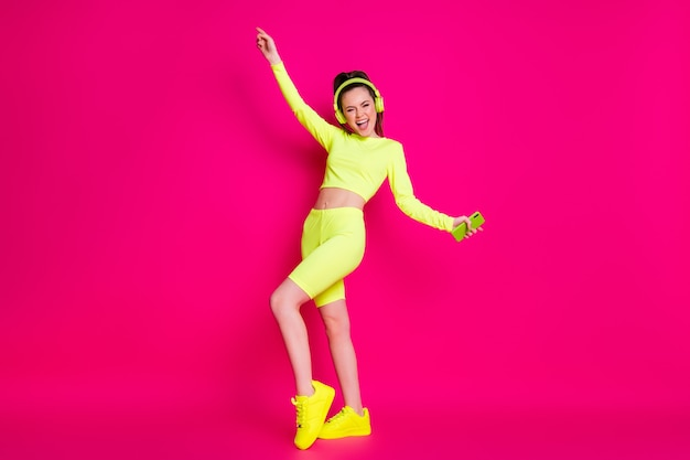 Full length body size view of her she nice attractive thin cheerful cheery glad girl listening music pop dancing having fun rest relax isolated bright vivid shine vibrant pink fuchsia color background