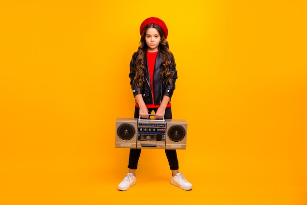 Full length body size view of her she nice attractive trendy confident long-haired girl in streetstyle holding in hands boombox isolated over bright vivid shine vibrant yellow color wall