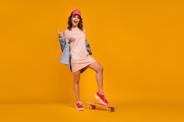 Full length body size view of her she nice-looking attractive lovely cool cheerful cheery girl standing on board showing horn symbol isolated on bright vivid shine vibrant yellow color background