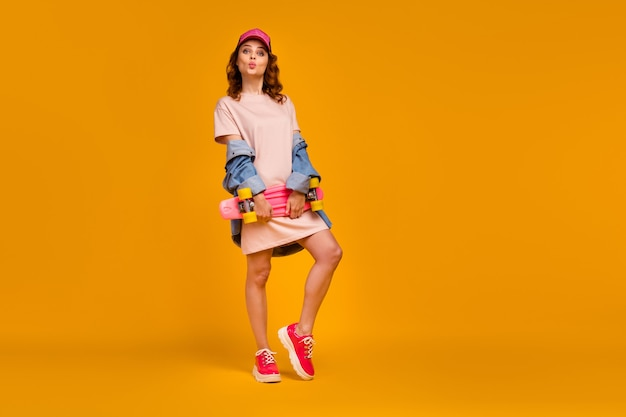 Full length body size view of her she nice-looking attractive lovely lovable flirty pretty cheerful girl carrying board sending air kiss isolated on bright vivid shine vibrant yellow color background