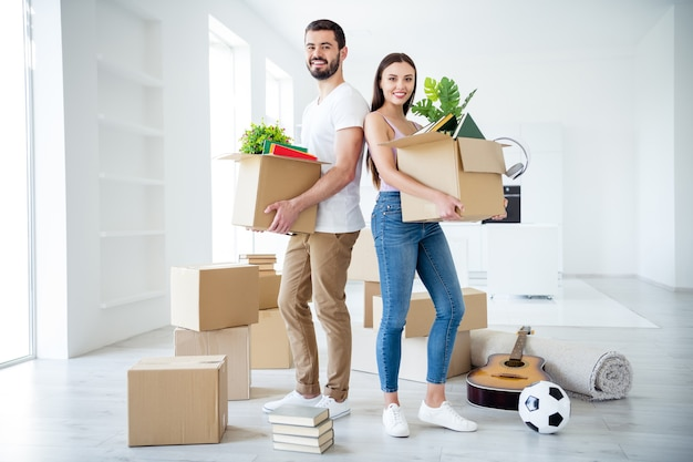 Full length body size view of his he her she nice attractive cheerful cheery casual stylish couple holding in hands stuff package settling down at place space flat light white interior house indoors
