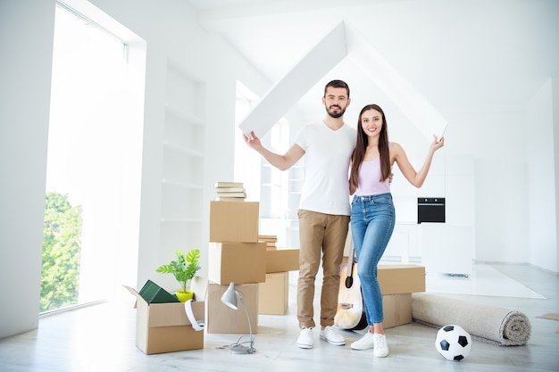 Full length body size view of his he her she nice attractive cheerful married spouses holding in hands wooden roof rent bank loan purchase building development at flat light white interior