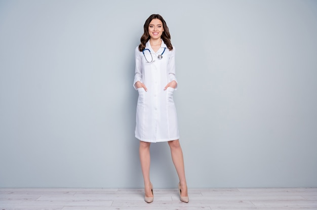 Full length body size view of nice attractive cheerful cheery confident qualified wavyhaired girl doc holding hands in pockets career clinic isolated over grey pastel color background