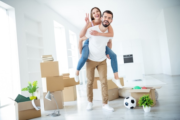 Full length body size view of nice attractive cheerful cheery couple piggy-backing showing v-sign purchase rent loan safety property insurance having fun at light white interior house indoors