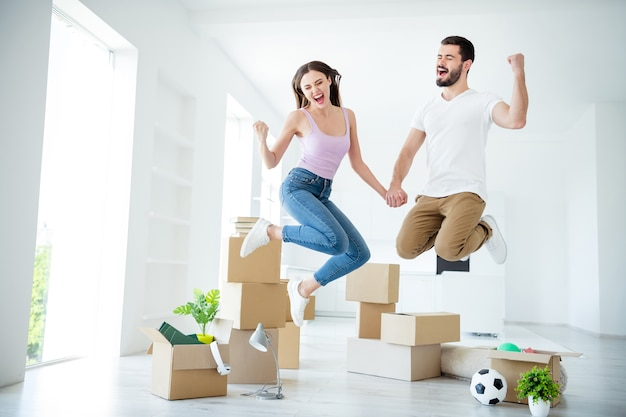 Full length body size view of nice attractive cheerful cheery overjoyed lucky couple jumping rejoicing purchase real-estate property having fun lottery winner at light white interior house indoors