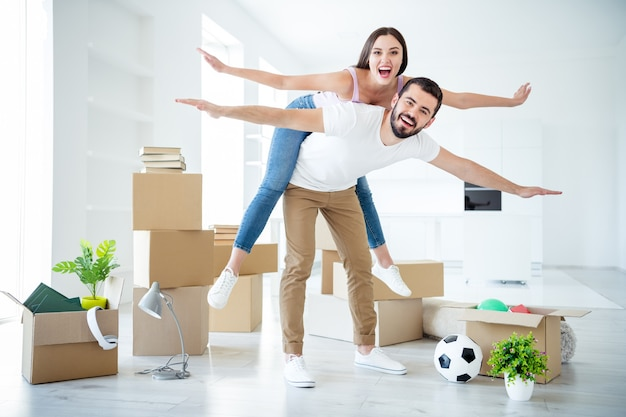 Full length body size view of nice attractive cheerful couple piggy-backing flying like plane purchase real-estate lease loan safety investment insurance travel trip at light white interior house