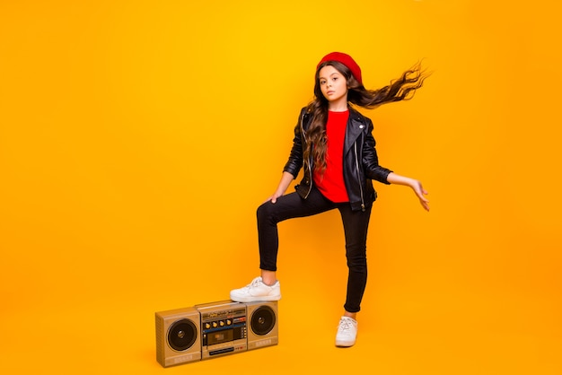 Full length body size view of nice attractive confident long-haired girl in streetstyle holding leg on boombox throwing hair enjoying isolated over bright vivid shine vibrant yellow color wall