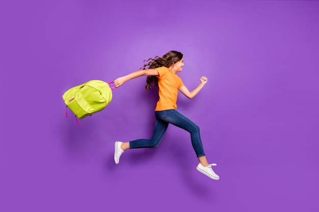 Full length body size view of nice attractive glad cheerful cheery wavy-haired girl jumping carrying bag running fast autumn fall september isolated on lilac purple violet pastel color background