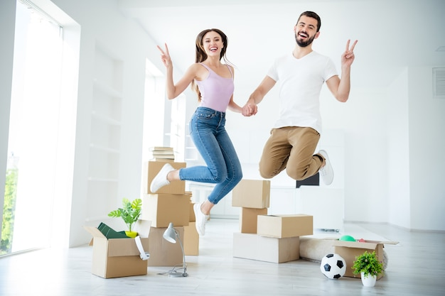 Full length body size view of nice attractive lovely glad cheerful cheery lucky couple jumping having fun showing v-sign loan safety property insurance at light white interior house apartment