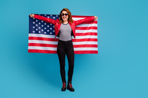 Full length body size view of nice attractive pretty cheerful cheery glad wavy-haired girl holding in hands usa flag learn english language isolated on bright vivid shine vibrant blue color background