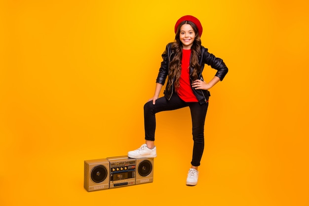 Full length body size view of nice attractive trendy cheerful long-haired girl in streetstyle holding leg on boombox rock party time isolated over bright vivid shine vibrant yellow color wall
