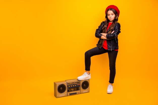 Full length body size view of nice attractive trendy fashionable long-haired girl in streetstyle standing near boombox folded arms isolated over bright vivid shine vibrant yellow color wall