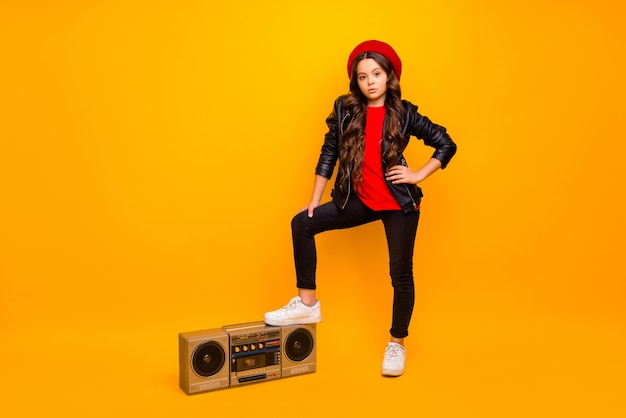 Full length body size view of nice attractive trendy long-haired girl in streetstyle holding leg on boombox pop rock heavy metal party isolated over bright vivid shine vibrant yellow color wall