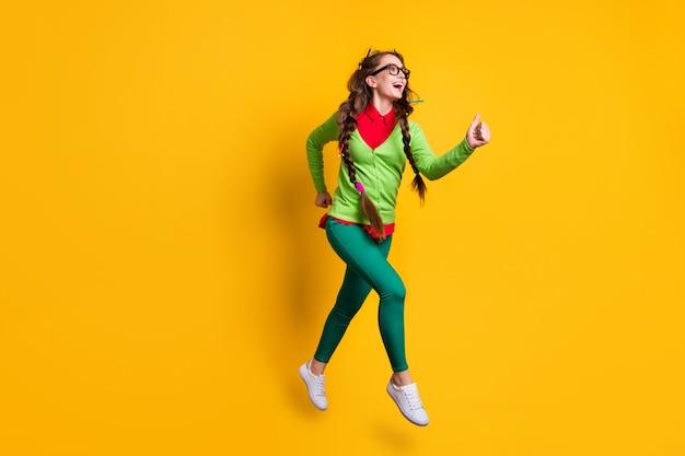 Вид в полный рост привлекательной веселой веселой девушки, прыгающей на бегу 1 сентября, изолировал ярко-желтый цвет фона