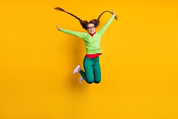 Вид в полный рост привлекательной фанк-экстатической веселой девушки, прыгающей с удовольствием, изолированной на ярко-желтом цветном фоне