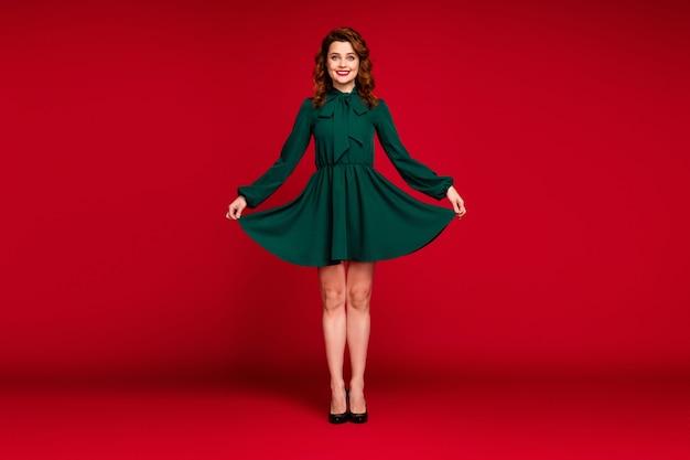 赤い栗色の色の背景で隔離の魅力的な素敵な女の子のポーズの全身サイズのビュー