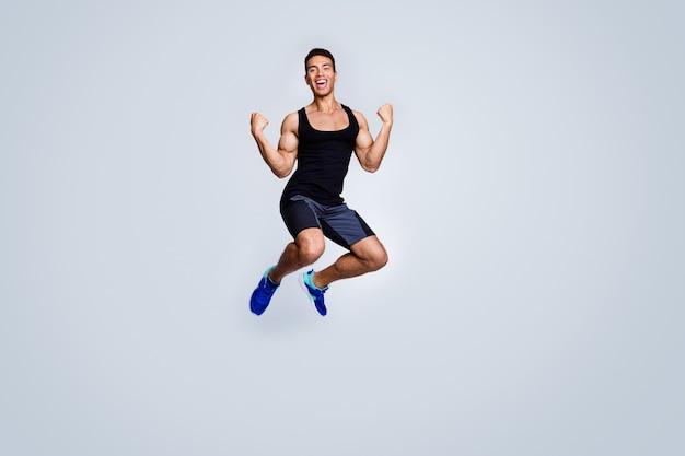 Вид в полный рост на привлекательного мускулистого спортивного парня, прыгающего, празднуя ликование