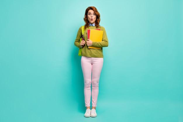 魅力的なスマート賢い驚いた陽気なウェーブのかかった髪の少女の全身サイズのビュー学校に戻る9月1日秋秋孤立した明るい鮮やかな輝き鮮やかなティールターコイズ色の背景