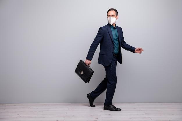 N95 안전 마스크 질병 질병 질병 메르스 cov 예방 중국 우한 고립 된 회색 배경을 입고 기업 세미나를 걷는 비즈니스 성숙한 남자의 전체 길이 신체 크기 보기