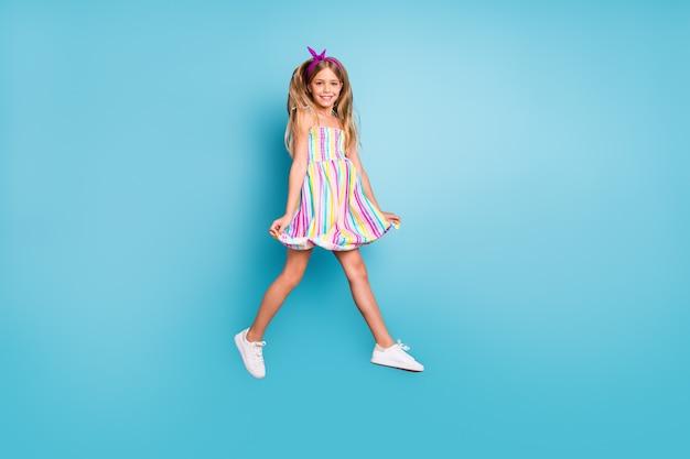 Вид в полный рост очаровательной милой веселой девушки, прыгающей на прогулке