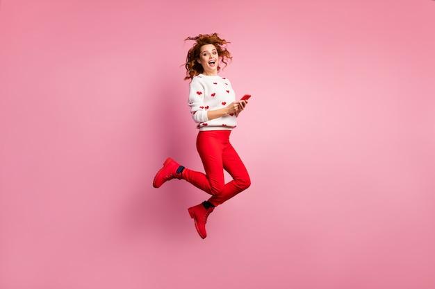 Smmのようなセルポストを使用してジャンプする陽気なセクシーな女の子のブロガーインフルエンサーの全身サイズのビュー