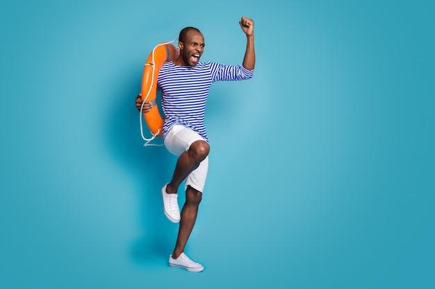 陽気な男の全身サイズのビューは、青い背景の上に分離されたゴム製の命の恩人を運ぶ