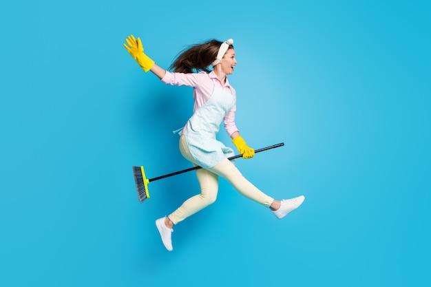 Веселая и радостная девушка, домработница, уборщица в полный рост, прыгает на метле