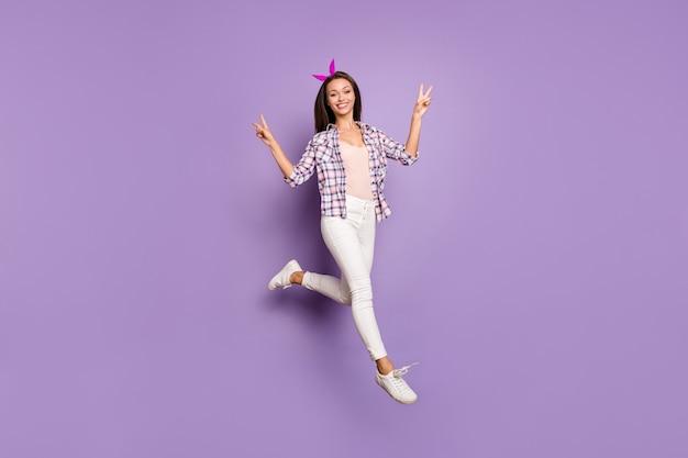 라일락 색 벽에 고립 된 v 기호를 보여주는 소녀 점프의 전체 길이 신체 크기보기