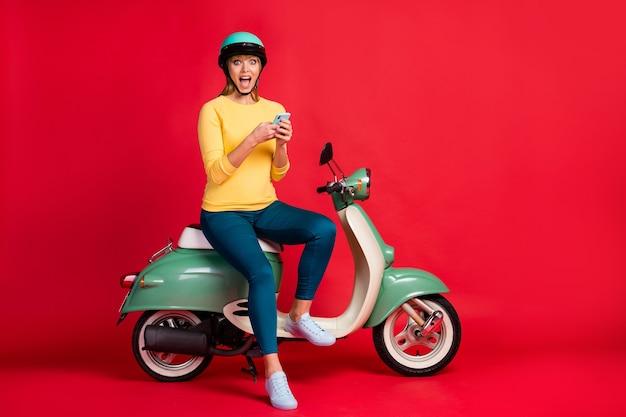 소녀의 전체 길이 몸 크기보기는 빨간 벽에 셀 오픈 입을 사용하여 오토바이에 앉아