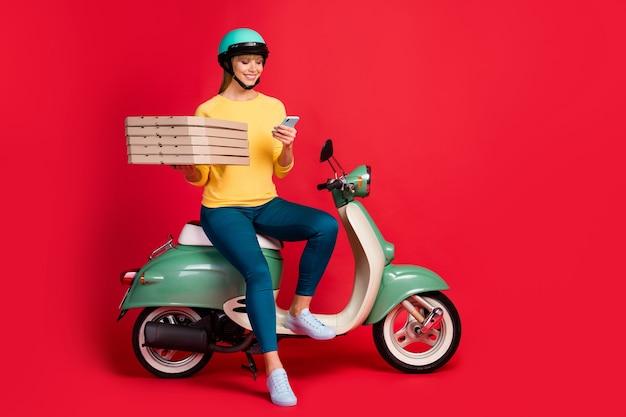 Вид в полный рост девушки, сидящей на мопеде, держите телефонные коробки для пиццы